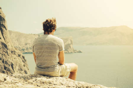 Young Man relaxing on rocky cliff  Sea and mountains on background Lifestyle Summer vacations concept retro colors Stock Photo
