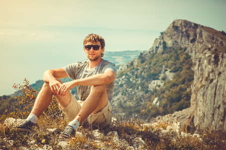 Young Man relaxing outdoor with mountains on background Summer vacations and Lifestyle hiking concept photo
