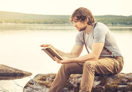 Jonge Man leesboek buiten met meer op de achtergrond Zomer vakanties en Lifestyle-concept