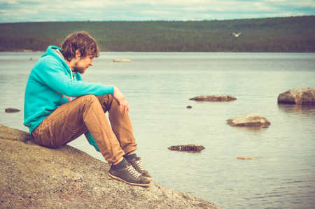 Young Man relaxing outdoor on mountain with lake on background Summer vacations and Lifestyle hiking concept photo