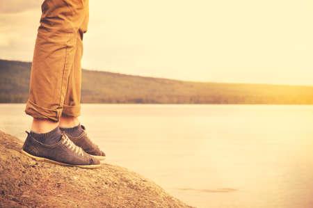 Pies hombre caminando al aire libre estilo de vida Vacaciones Viajes concepto con el lago y el sol en el fondo de colores retro