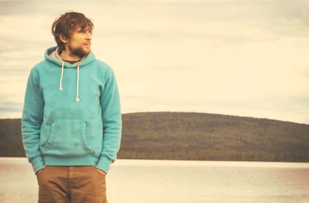 Young Man hipster standing alone outdoor with mountains and lake on background Lifestyle and melancholy emotions concept photo