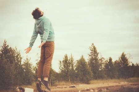 若い男を飛んで浮上ジャンプ屋外リラックス ライフ スタイル幸福精神的な概念レトロ フィルム色トレンディなスタイル 写真素材