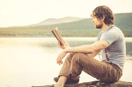 A leitura do livro do homem novo ao ar livre com lago em f Banco de Imagens