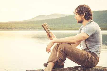 Young Man reading book outdoor with lake on background Summer vacations and Lifestyle concept Imagens - 31576483