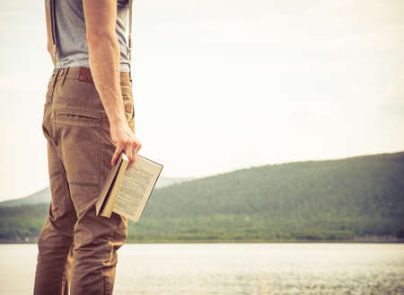 Young Man with book outdoor lake on background Summer vacations and Lifestyle concept Imagens