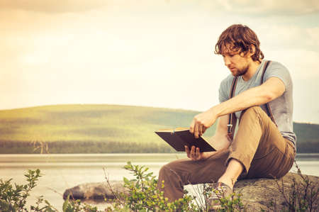 Libro de lectura de hombre joven al aire libre con el lago en las vacaciones de verano de fondo y el concepto de estilo de vida