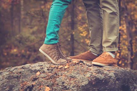 カップルの男性と女性足愛ロマンチックな屋外ファッションのトレンディなスタイルの背景に秋の季節の自然と