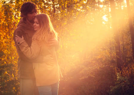 Young Couple Man and Woman Hugging in Love Romantic Outdoor with sun light Autumn nature on background Fashion trendy style