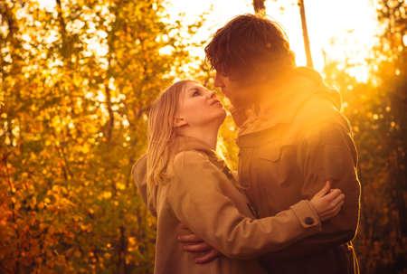 enamorados besandose: Pareja joven hombre y la mujer abrazando y besando en el amor romántico al aire libre con la naturaleza la luz del sol de otoño en el fondo de la manera estilo de moda