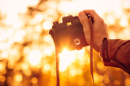Man hand holding retro photo camera outdoor hipster Lifestyle with sun lights bokeh autumn nature on background Stock Photo