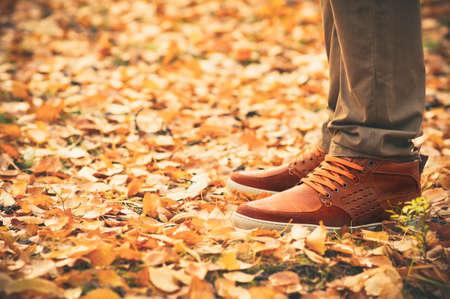 Pés Homem que anda nas folhas da queda ao ar livre com estação do outono natureza no fundo Lifestyle Moda estilo na moda