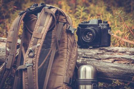 Attrezzature da campeggio trekking Stile di vita retrò macchina fotografica zaino ed esterni della natura foresta sullo sfondo Archivio Fotografico