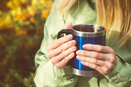 Metal touristic tea cup in Woman hands Outdoor Lifestyle and Hiking concept with forest on background photo