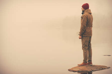 man standing alone: Young Man standing alone outdoor with foggy scandinavian nature on background Travel Lifestyle and melancholy emotions concept film effects colors Stock Photo