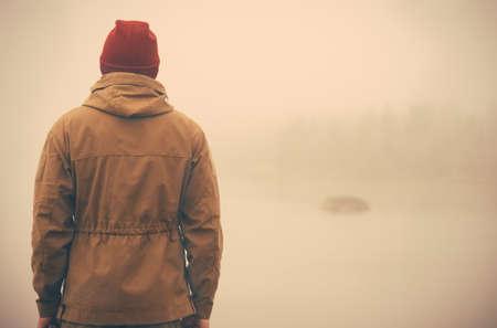 Jonge Mens die zich alleen buiten met mistige Scandinavische natuur op de achtergrond Reizen Lifestyle en melancholie emoties concept filmeffecten kleuren