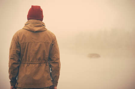 Young Man standing alone outdoor with foggy scandinavian nature on background Travel Lifestyle and melancholy emotions concept film effects colors Stock Photo