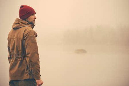 Giovane uomo in piedi da solo all'aperto con nebbia natura scandinava su Lifestyle sfondo di viaggio e emozioni malinconiche concetto di film Effetti colori