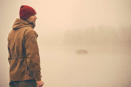 Young Man standing alone outdoor with foggy scandinavian nature on background Travel Lifestyle and melancholy emotions concept film effects colors Imagens