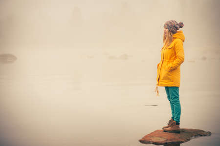 standing alone: Young Woman standing alone outdoor Travel Lifestyle and melancholy emotions concept  winter foggy nature on background Stock Photo