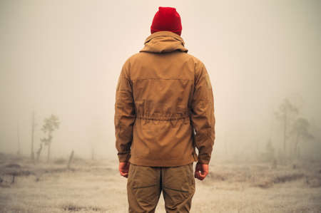 Young Man standing alone outdoor with foggy scandinavian nature on background Travel Lifestyle and melancholy emotions concept film effects colors photo