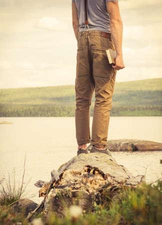 Hombre joven con el libro La educación al aire libre y estilo de vida Viajes concepto de naturaleza en el fondo Foto de archivo