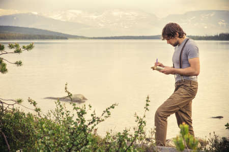 Young Man Traveler reading book and writing notes outdoor mountains on background Summer vacations and Lifestyle concept Imagens