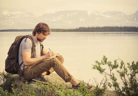 persona escribiendo: Jóvenes viajeros de Hombre con mochila leer el libro y la redacción de notas montañas al aire libre en fondo de las vacaciones de verano y el concepto de estilo de vida