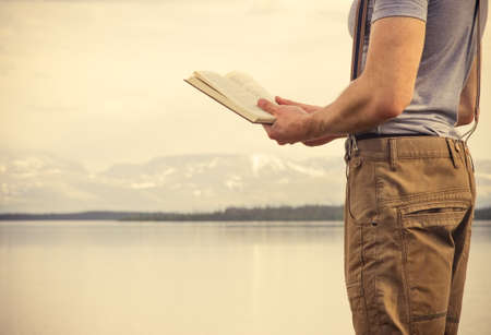 Young Man reading book outdoor with mountains on background Education and Lifestyle Travel concept photo