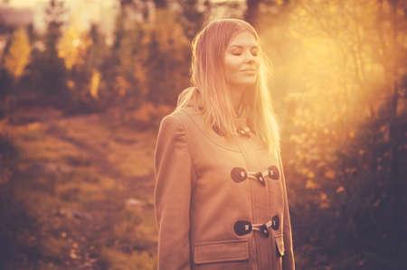 自然との調和自然太陽光屋外ライフ スタイル旅行秋の森の背景に笑顔と幸せな若い女性 写真素材