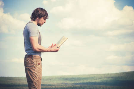 sky  clouds: Young Man Traveler reading book outdoor Travel Lifestyle concept sky clouds on background Stock Photo