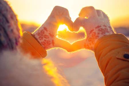 reisen: Frau, die Hände in den Winterhandschuhen Herzsymbol förmigen Lifestyle und Gefühle Konzept mit Sonnenuntergang Licht auf die Natur Hintergrund