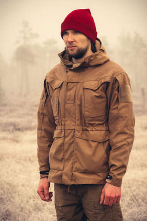 brown clothes: Young Man wearing winter hat clothing outdoor with foggy nature on background Travel Lifestyle and melancholy emotions concept film effects colors