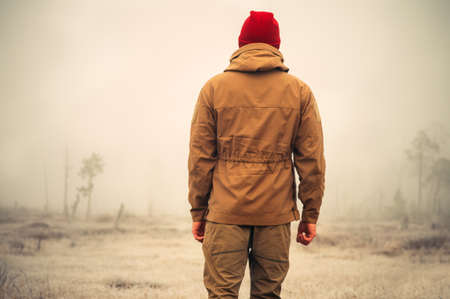 Giovane uomo in piedi da solo all'aperto con nebbia natura scandinava su Lifestyle sfondo di viaggio e emozioni malinconiche concetto cinematografiche effetti colori