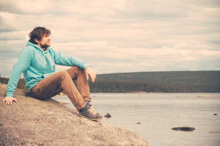 Young Man Traveler relaxing alone outdoor Lifestyle concept with mountains and lake on background