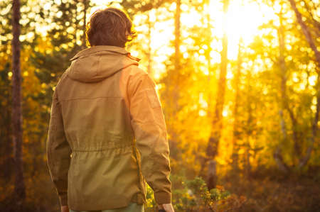 man standing alone: Young Man standing alone in forest outdoor with sunset nature on background Travel Lifestyle and survival concept