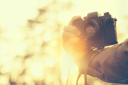 Man hand holding retro photo camera outdoor hipster Lifestyle with sunset lights on background film colors. Stock Photo