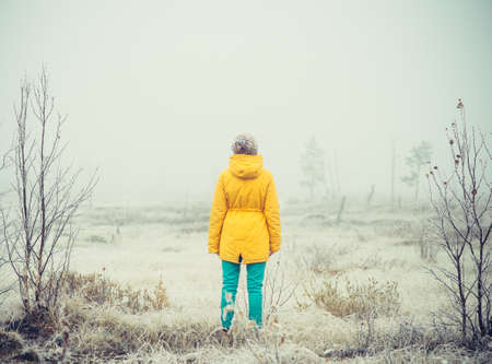 Young Woman standing alone outdoor Travel Lifestyle and melancholy emotions concept  winter foggy nature on background film effects colors Stock Photo