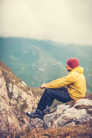 Bemannen Sie den Reisenden, der sich allein in der bewölkten Naturlandschaft des Gebirgs-Reise-Lebensstilkonzeptes auf Hintergrund entspannt