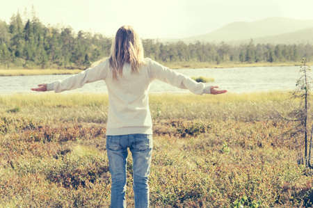 raised hands: Young Woman raised hands standing alone walking outdoor Travel Lifestyle scandinavian forest nature on background