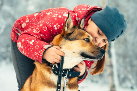 zoo youth: Girl Child and Dog hugging and playing Outdoor Lifestyle Friendship concept Winter nature on background Stock Photo