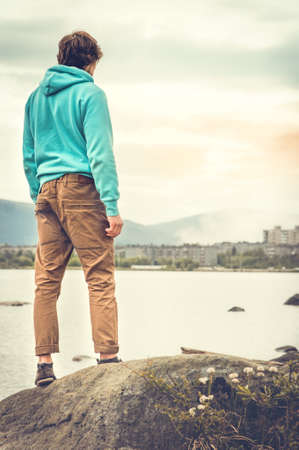 man standing alone: Young Man standing alone outdoor Travel Lifestyle concept with lake and city on background
