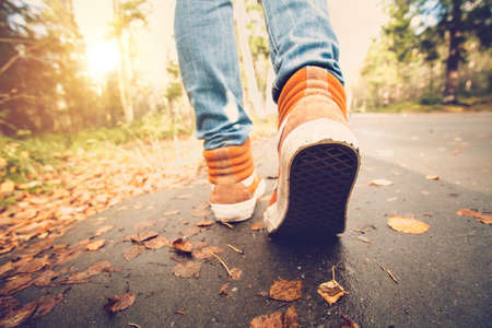 Donna piedi scarpe da ginnastica che camminano su fogli di caduta all'aperto con l'autunno la stagione della natura su sfondo Lifestyle Moda stile trendy