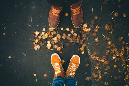 human relationships: Couple Man and Woman Feet in Love Romantic Outdoor with Autumn leaves on background Lifestyle Fashion concept