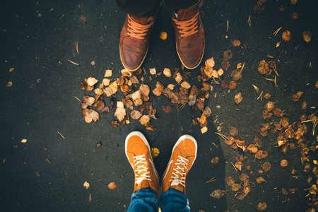 Autumn: Pareja hombre y de la mujer de pies en el amor romántico al aire libre con hojas de otoño en el fondo concepto de estilo de vida Moda