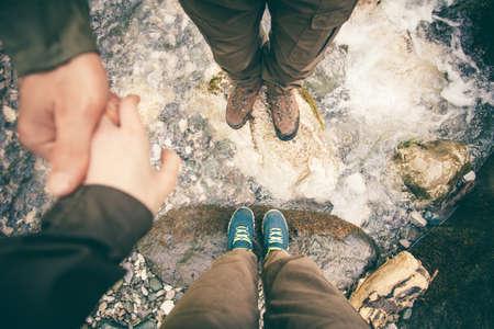 pies masculinos: Los pies del hombre y de la mujer en el amor de la mano de senderismo estilo de vida al aire libre de piedras Viajes y relación de conceptos río y en el fondo vista desde arriba