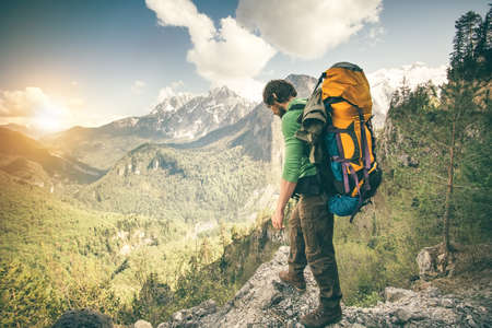 Young Man with backpack relaxing outdoor Travel Lifestyle hiking concept with rocky mountains on background Summer vacations