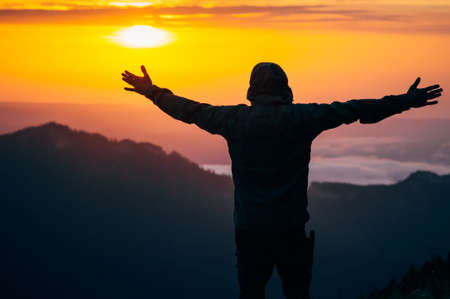 hands raised sky: Man Traveler hands raised silhouette outdoor with sunset sky mountains on background Travel Lifestyle and happiness emotions concept Foto de archivo