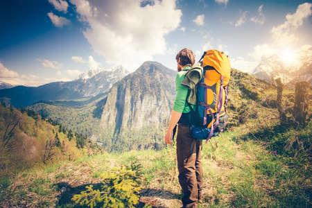 Молодой человек путешественник с рюкзаком отдыха на открытом воздухе с скалистых гор на фоне летних каникул и образ жизни, походы концепции