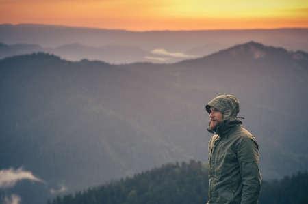Mladý muž s plnovousem samostatně stojící venku při západu slunce horami na pozadí jezdit životní styl a pojetí přežití